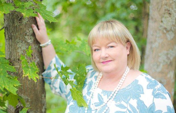 Aspa Palvelujen toimitusjohtaja Johanna Nyström nojaa vaahteraan kauniina kesäpäivänä.